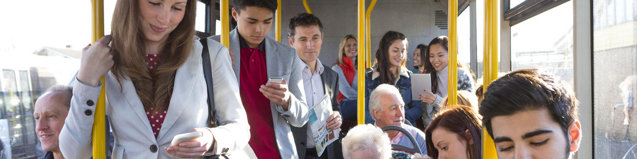 Bild vergrößern: Mixed group of pedestrians using technology on the bus.